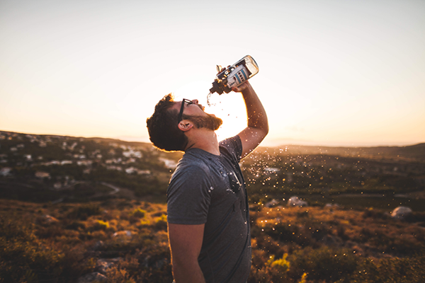 hiker chugs water from a hydroflask