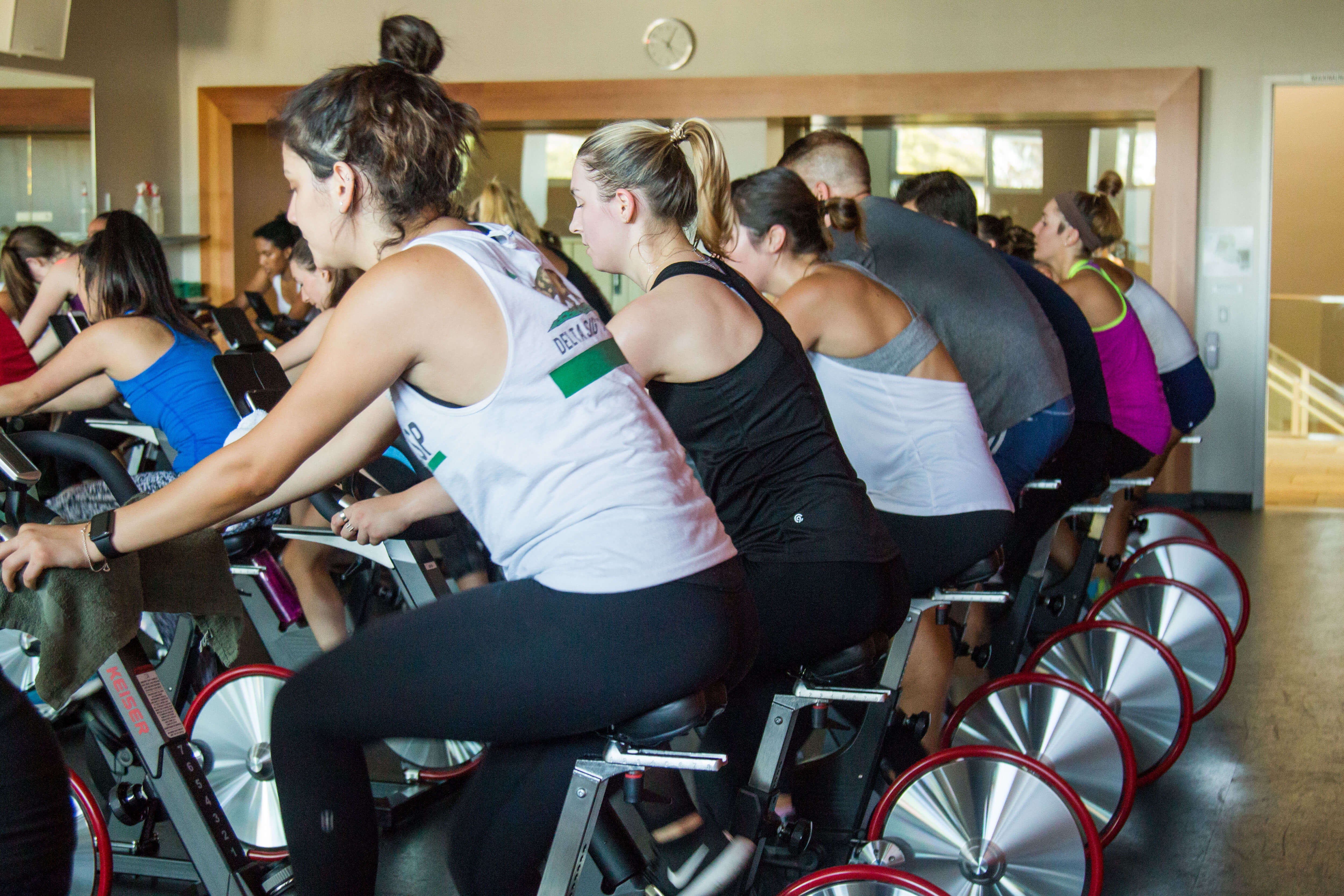 Students participate in an indoor cycling class