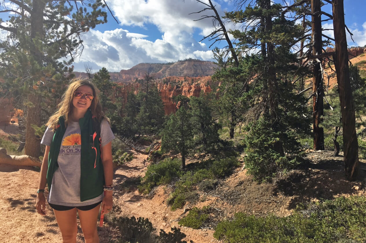 Rachel Shaw on a hiking trail next to trees and a cliffside