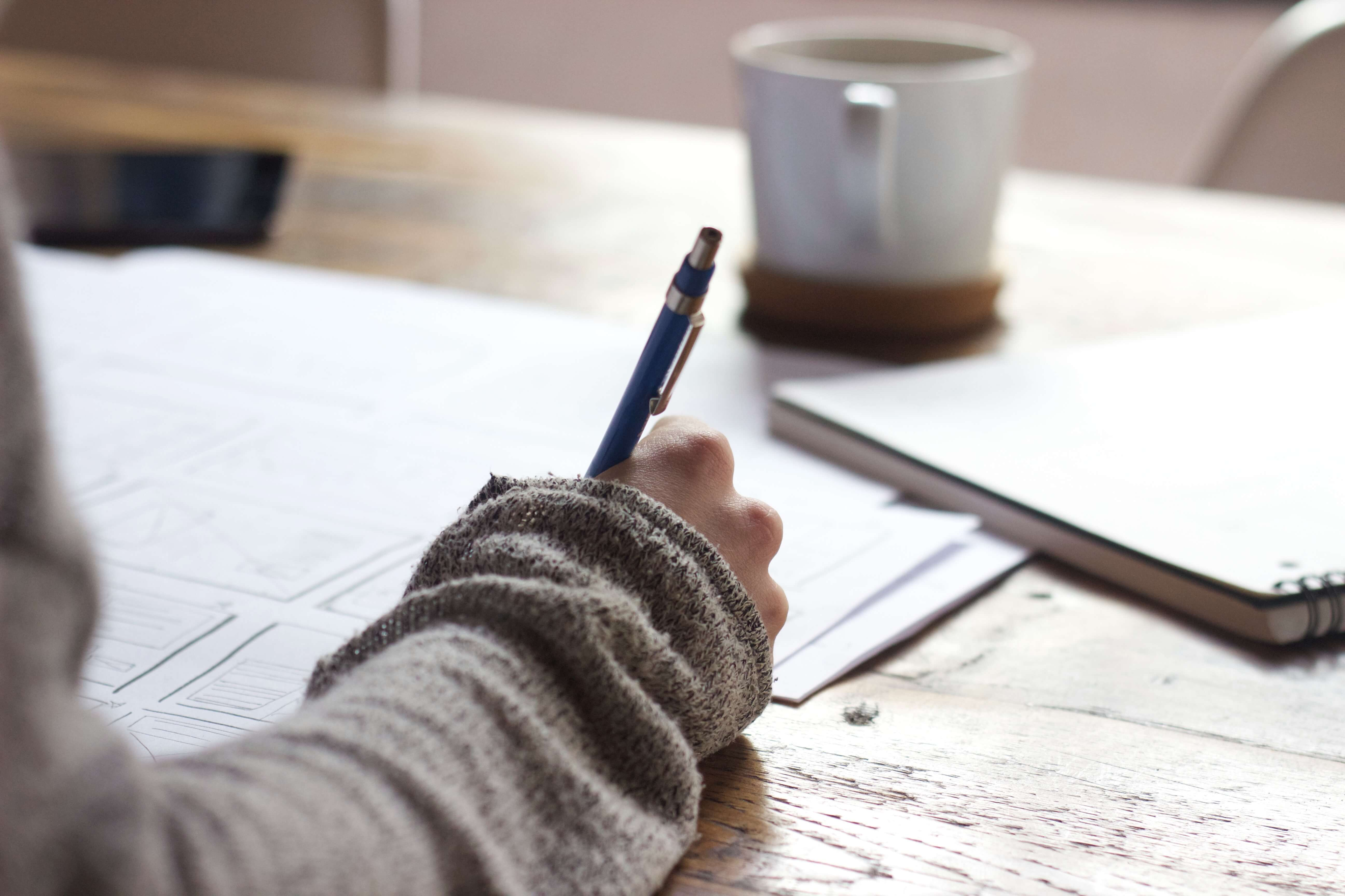 Close up of someone writing with a gray sleeve and a blue pen.