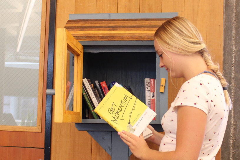 Female student pulling a book out of the Little Free Library titled Get Momentum