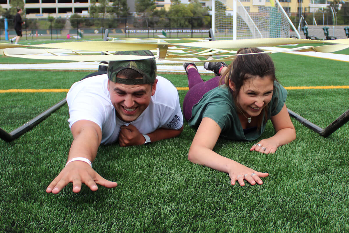 Male and female student on grass participating in an army crawl obstacle