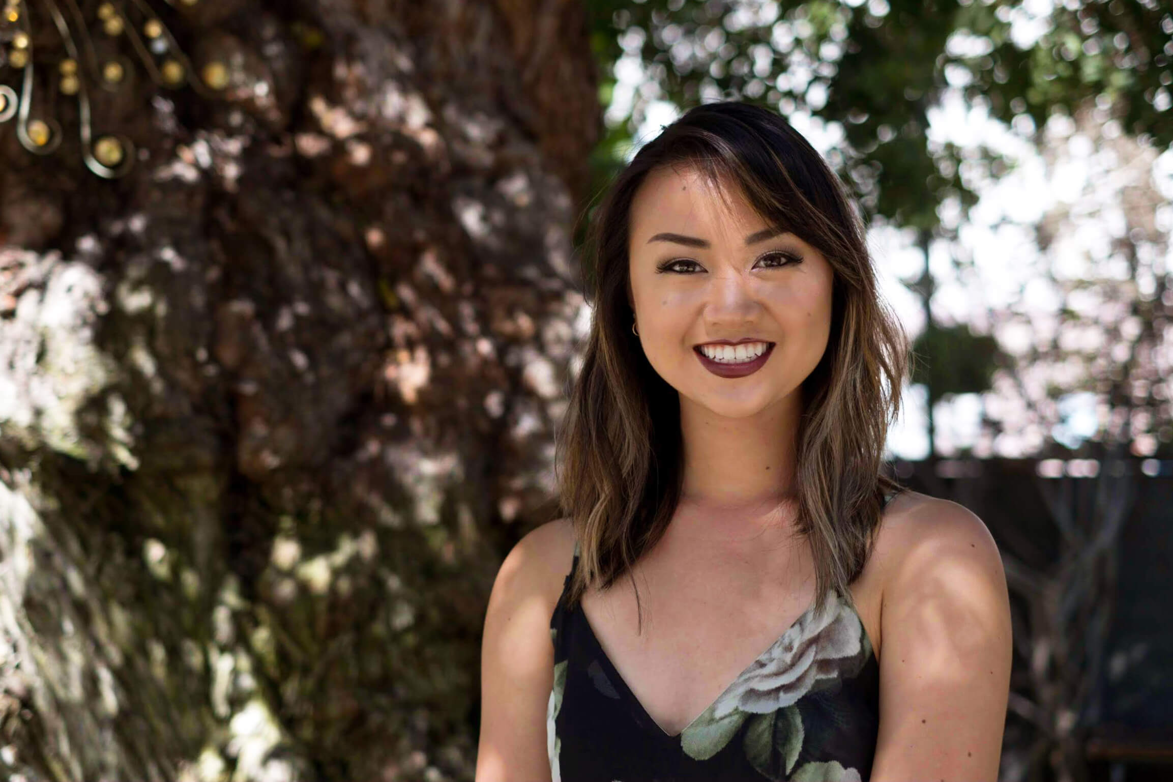 ASI student staff member Jackie Nguyen sits in front of a tree and smiles