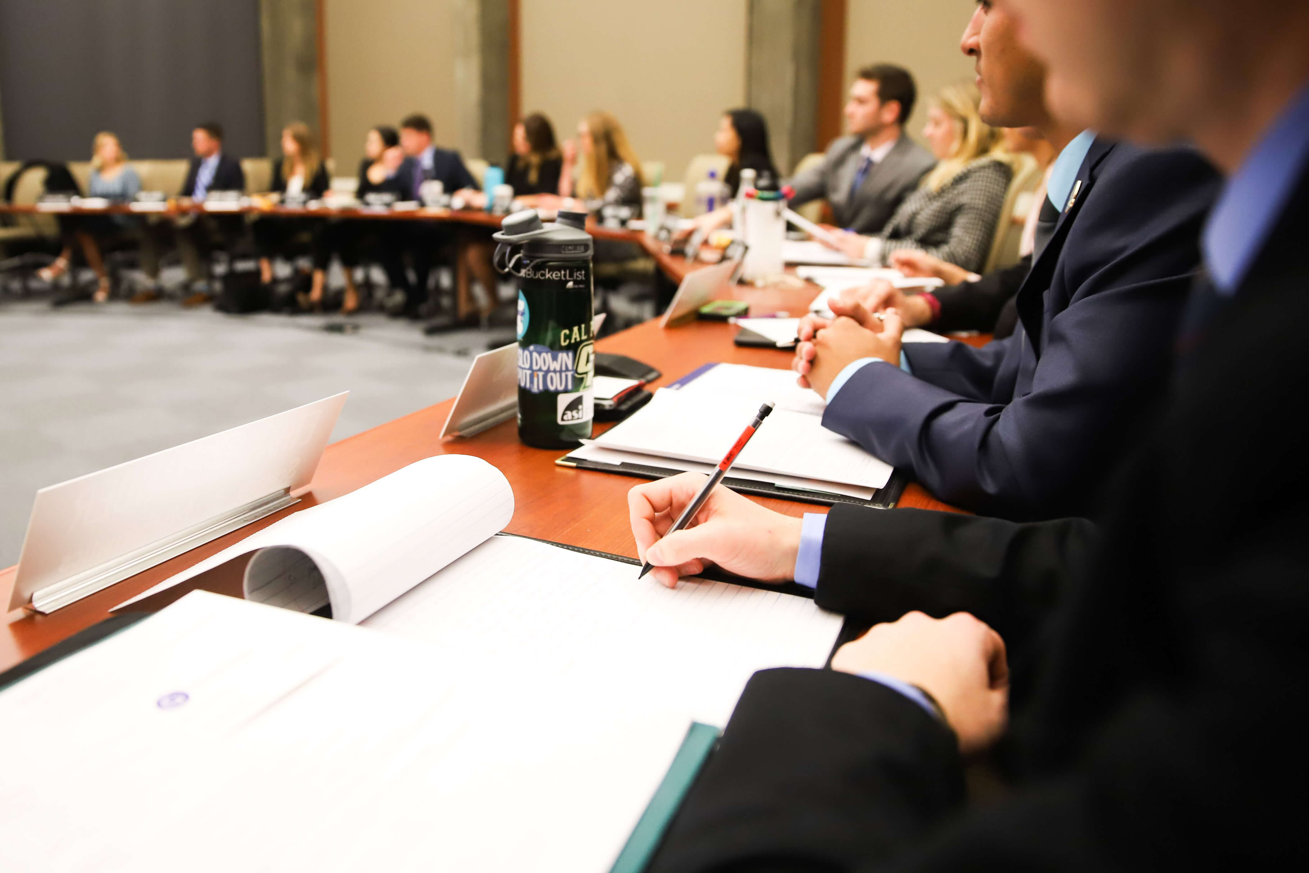 A student takes notes while others listen during a meeting