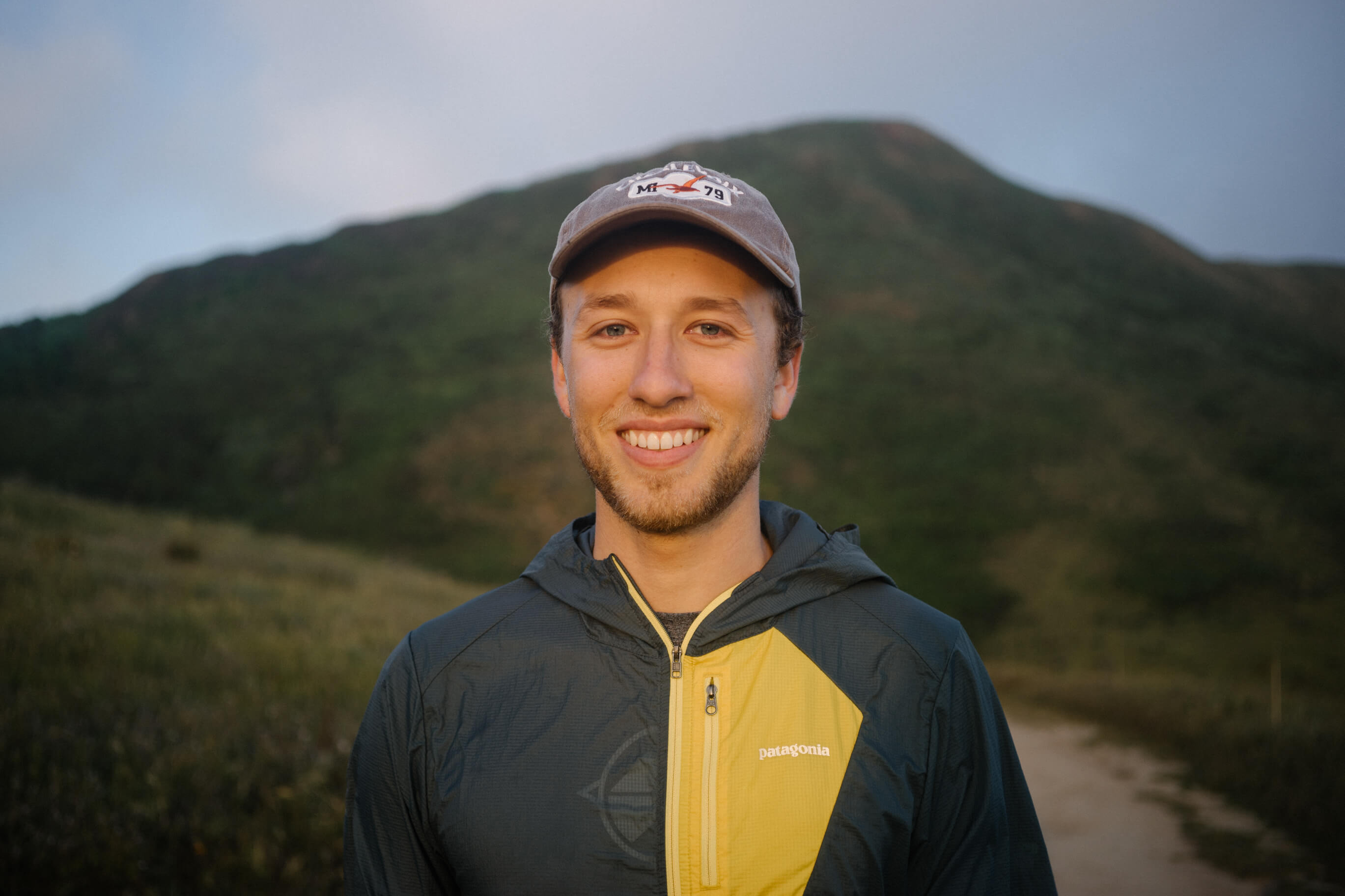 Alex Depue stands outside in front of a green hill and smiles