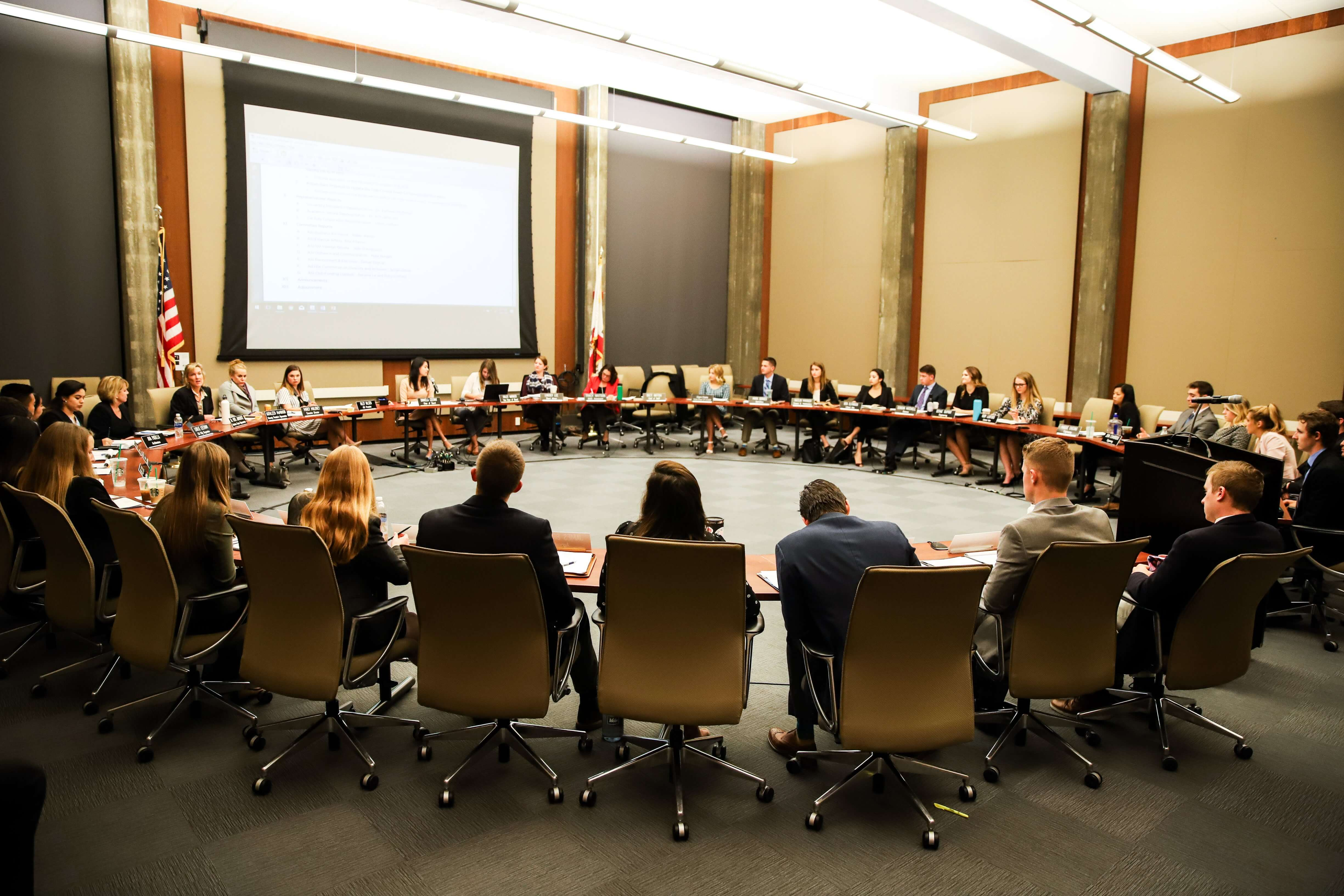 Students sit in a circular table at an ASI Board of Directors meeting
