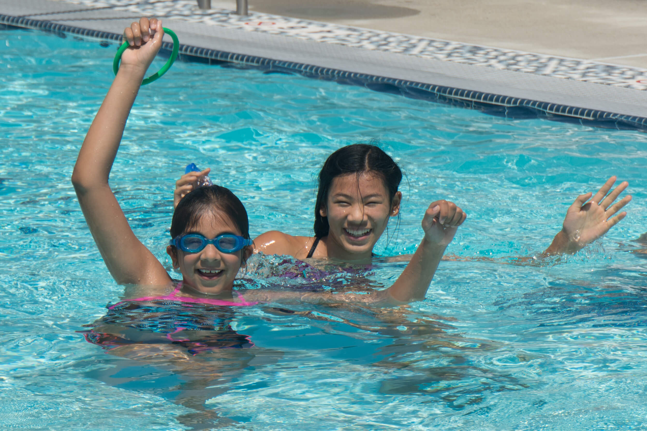 Two children smiling while swimming in the pool and holding ring toys