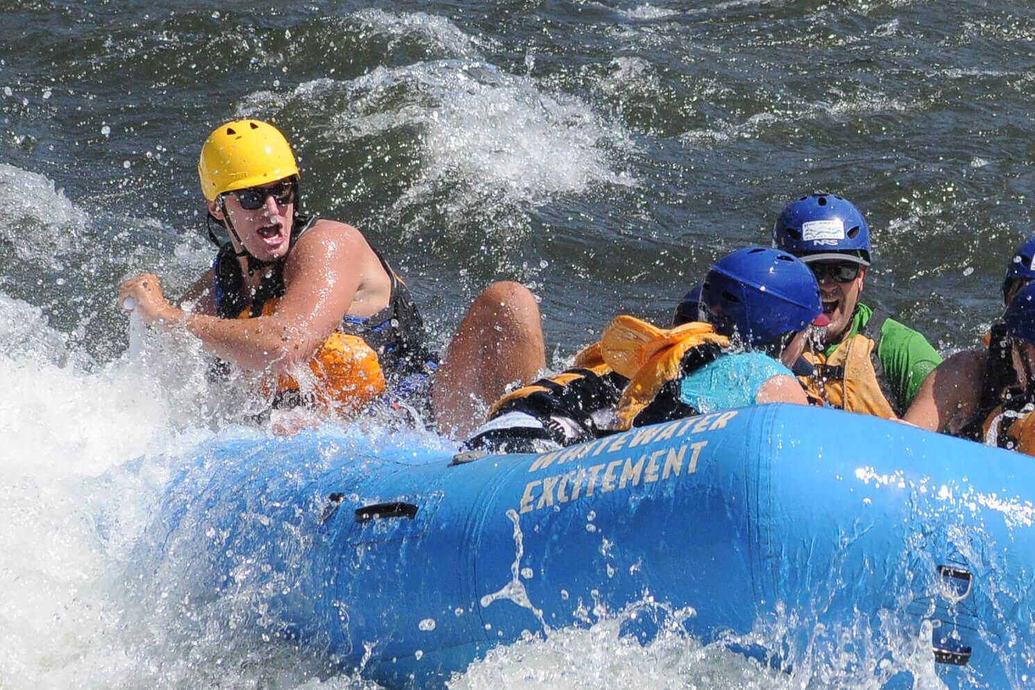 Jake Watkins smiles while whitewater rafting through a rapid