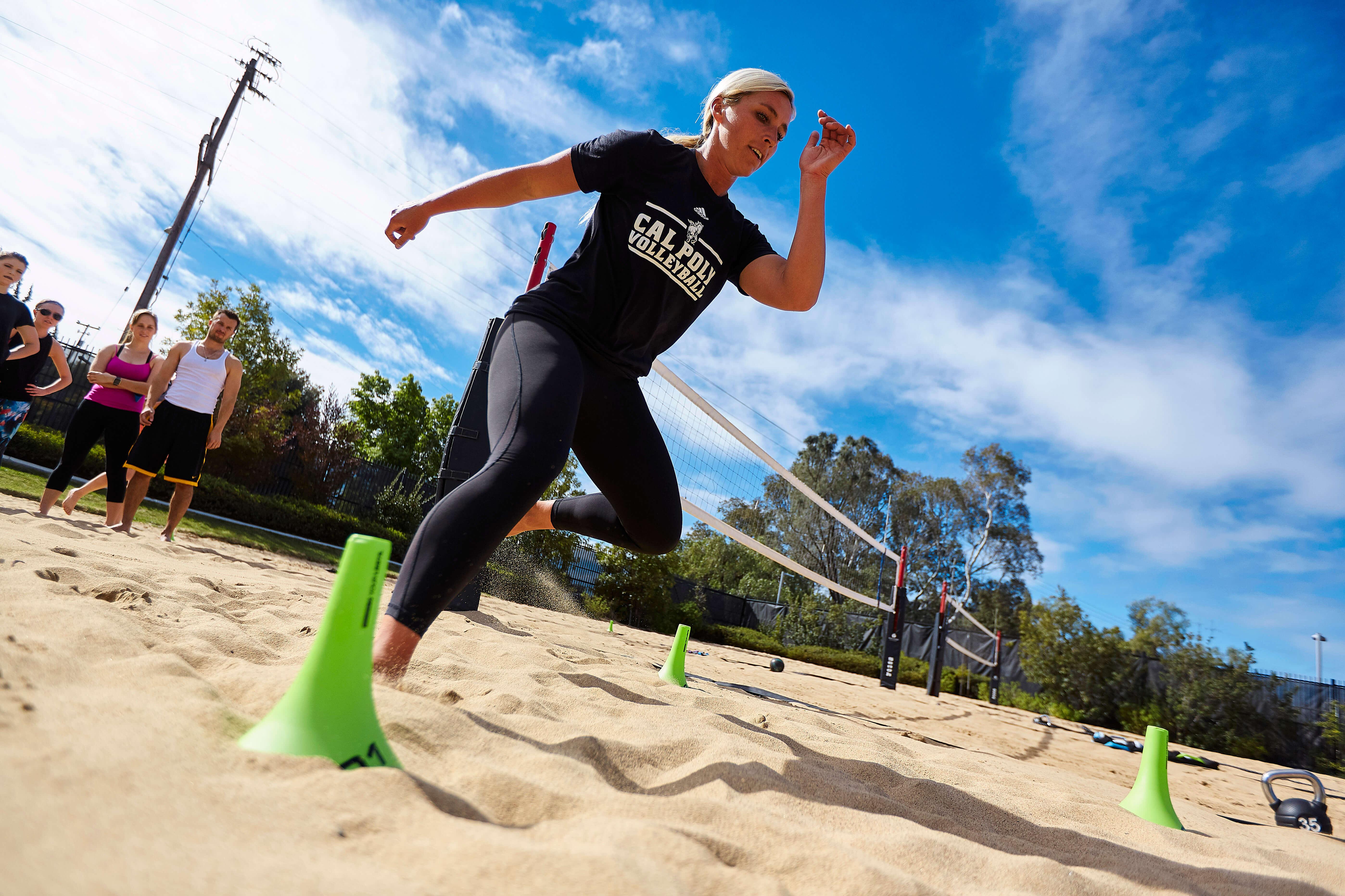 A female Beach Bootcamp participant runs through the sand around green cones