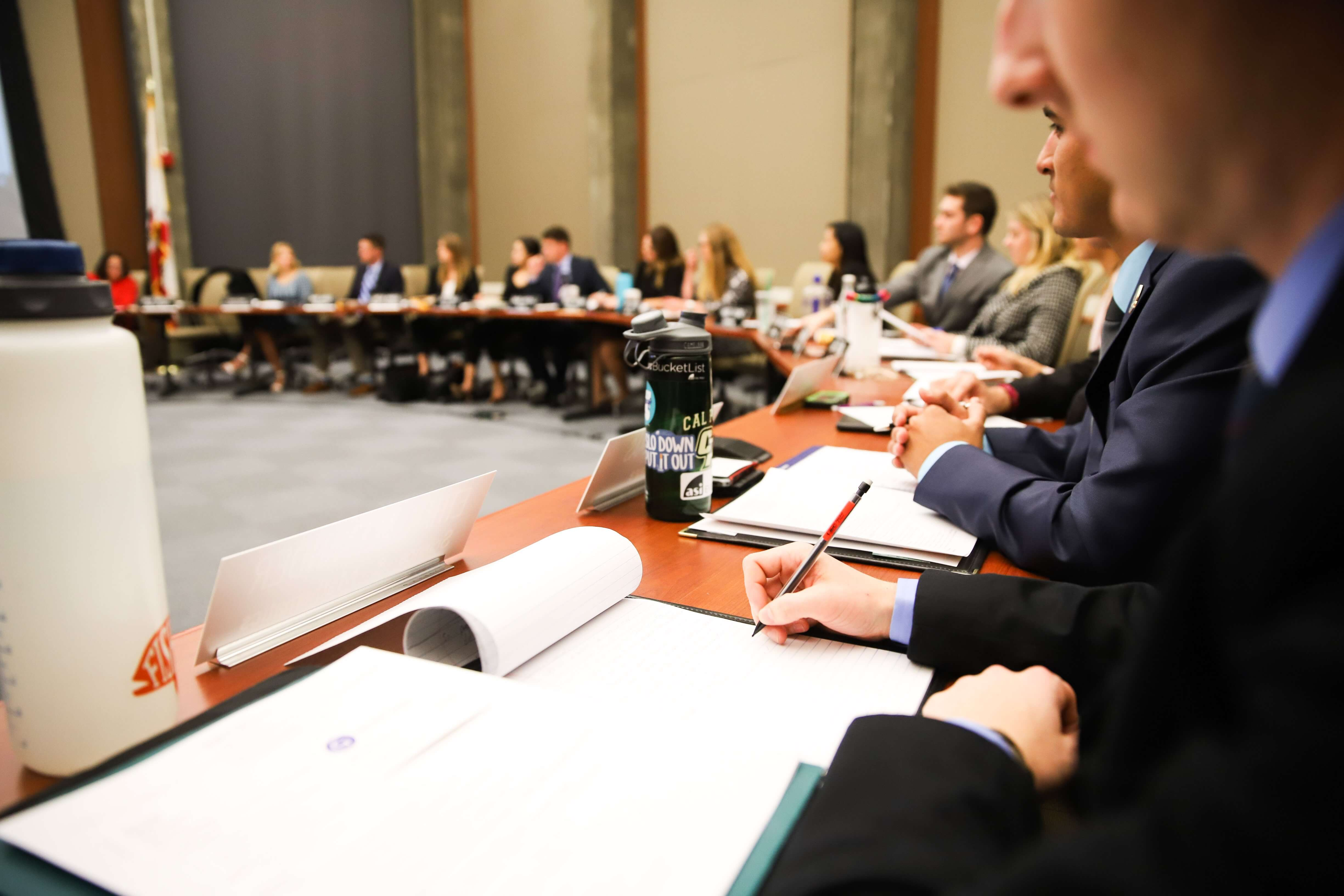 A student takes notes at a round table during an ASI Board of Directors meeting