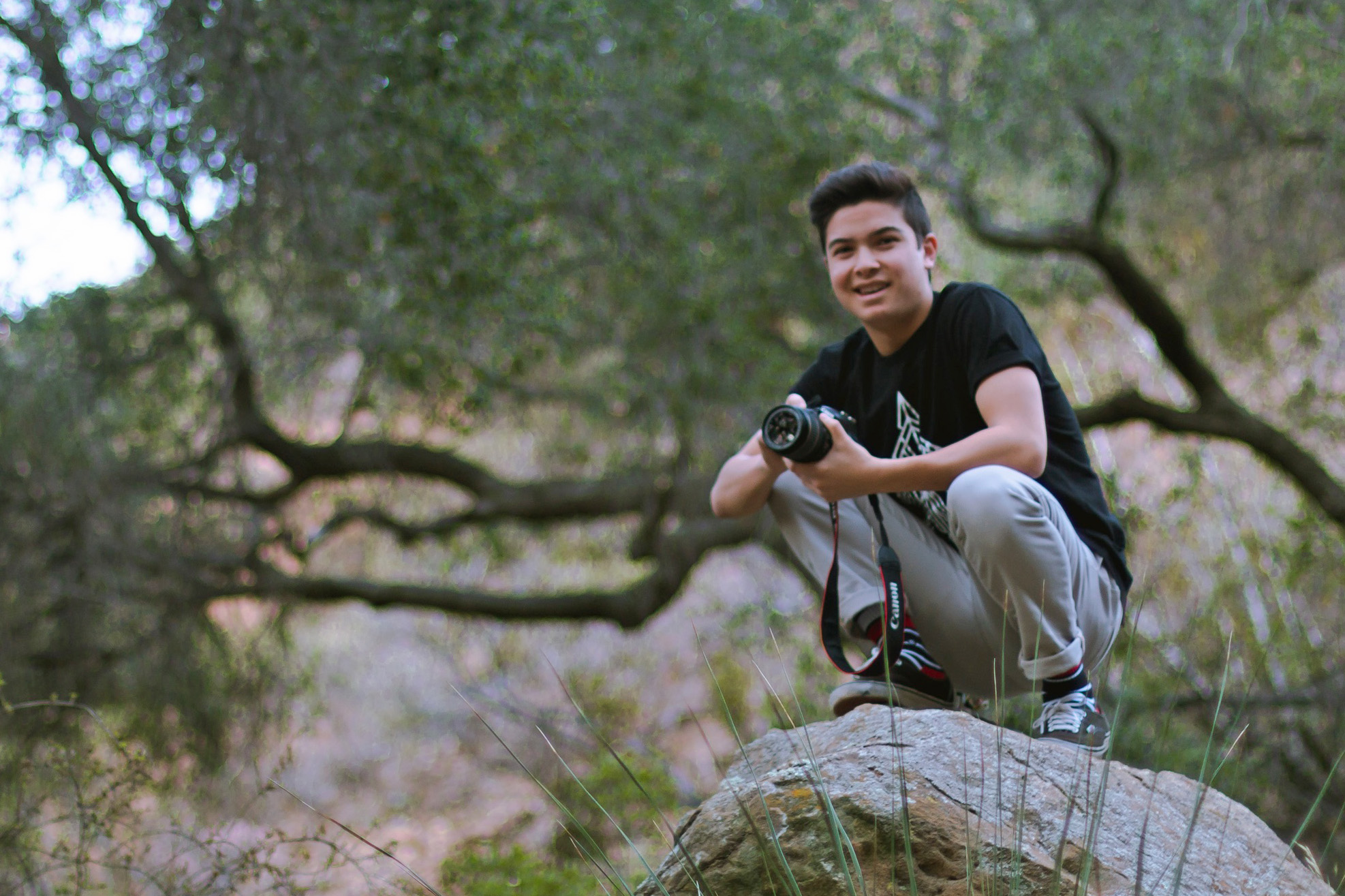 Noah Miyake smiles while holding a camera and squatting on a rock in front of a large oak tree