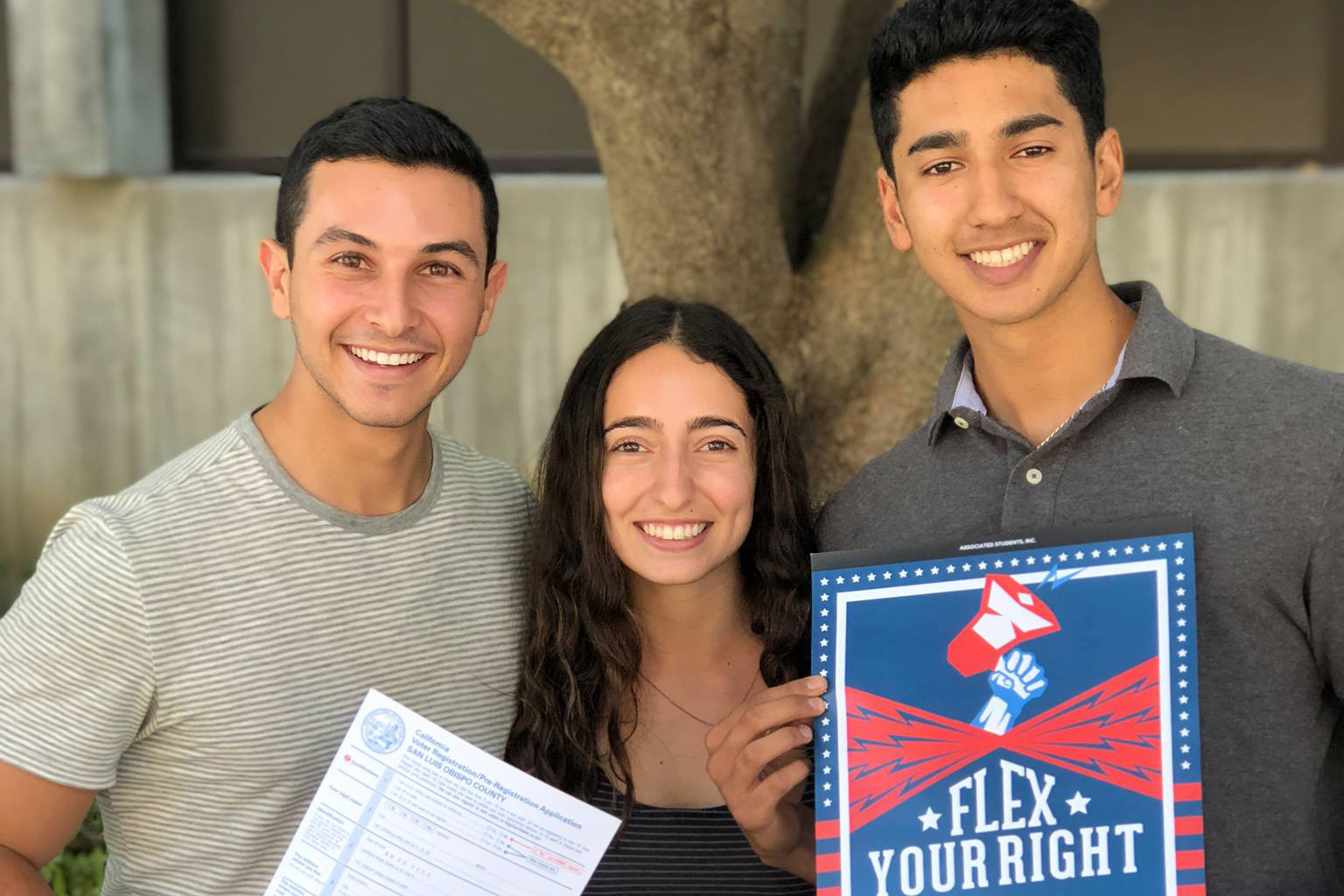 Two male students and a female student smile while holding a Flex Your Right red, white, and blue poster