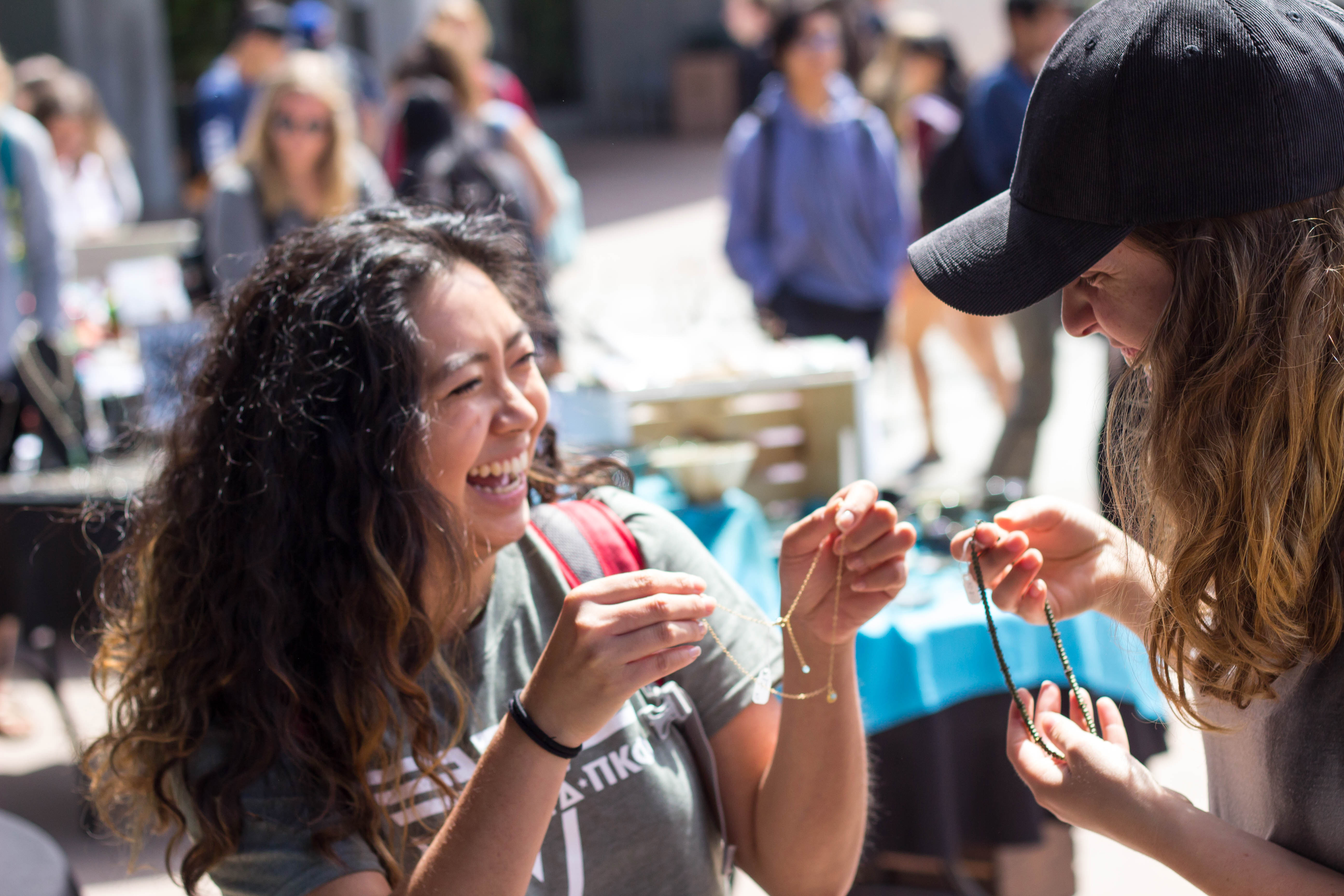 Two female students smile while holding up necklaces at the Craft Sale
