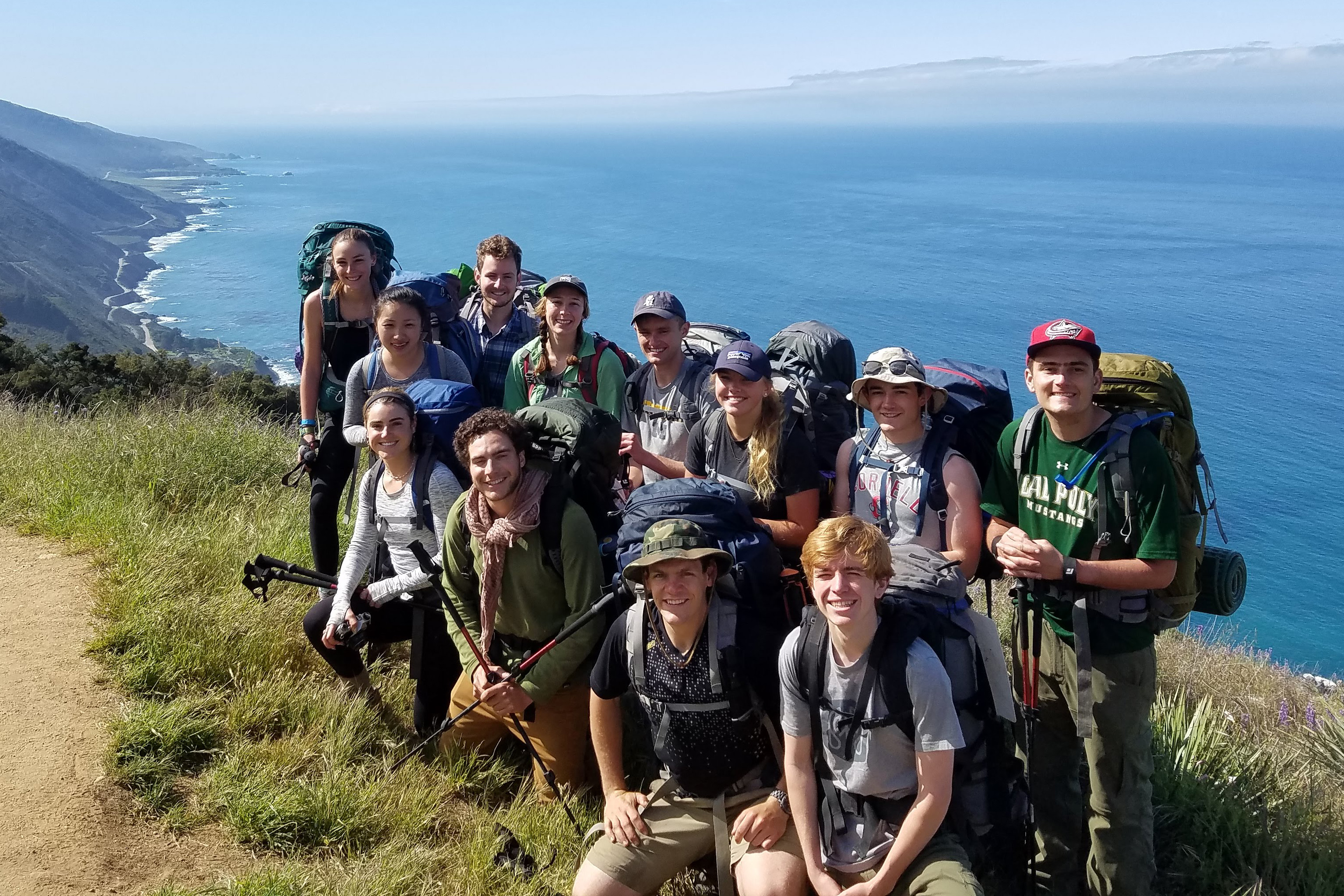 A group of students smile while standing in front of the Big Sur coastline