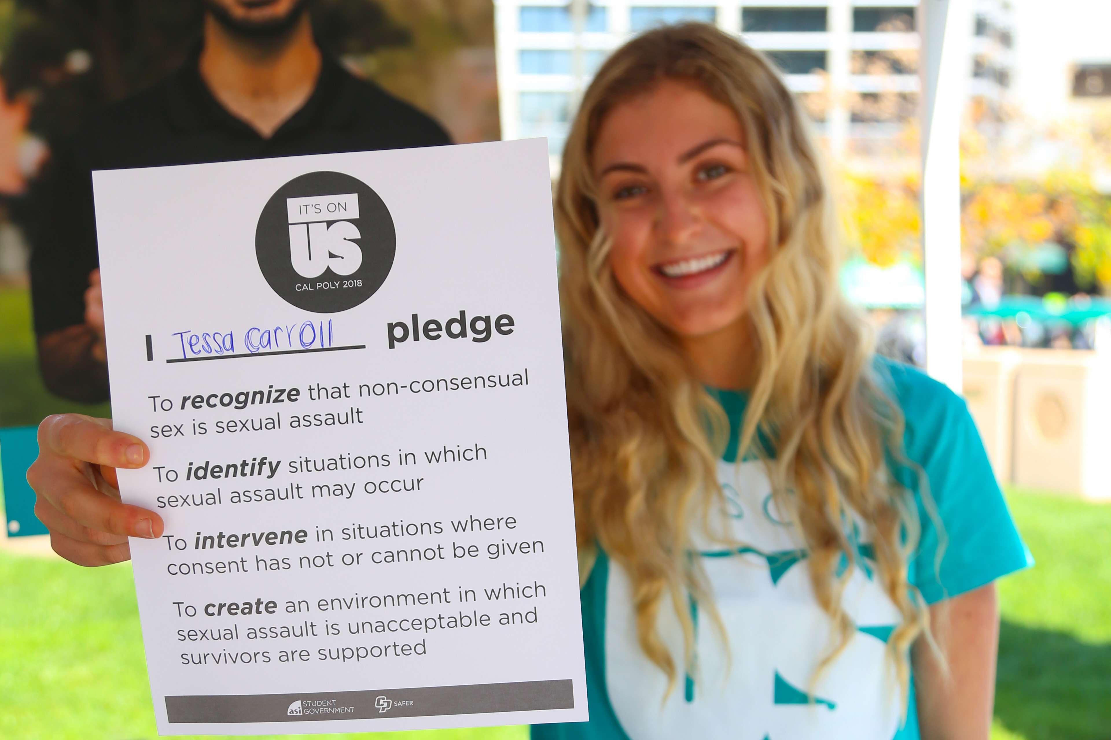A female student holds up a paper of the It's On Us pledge against sexual assault