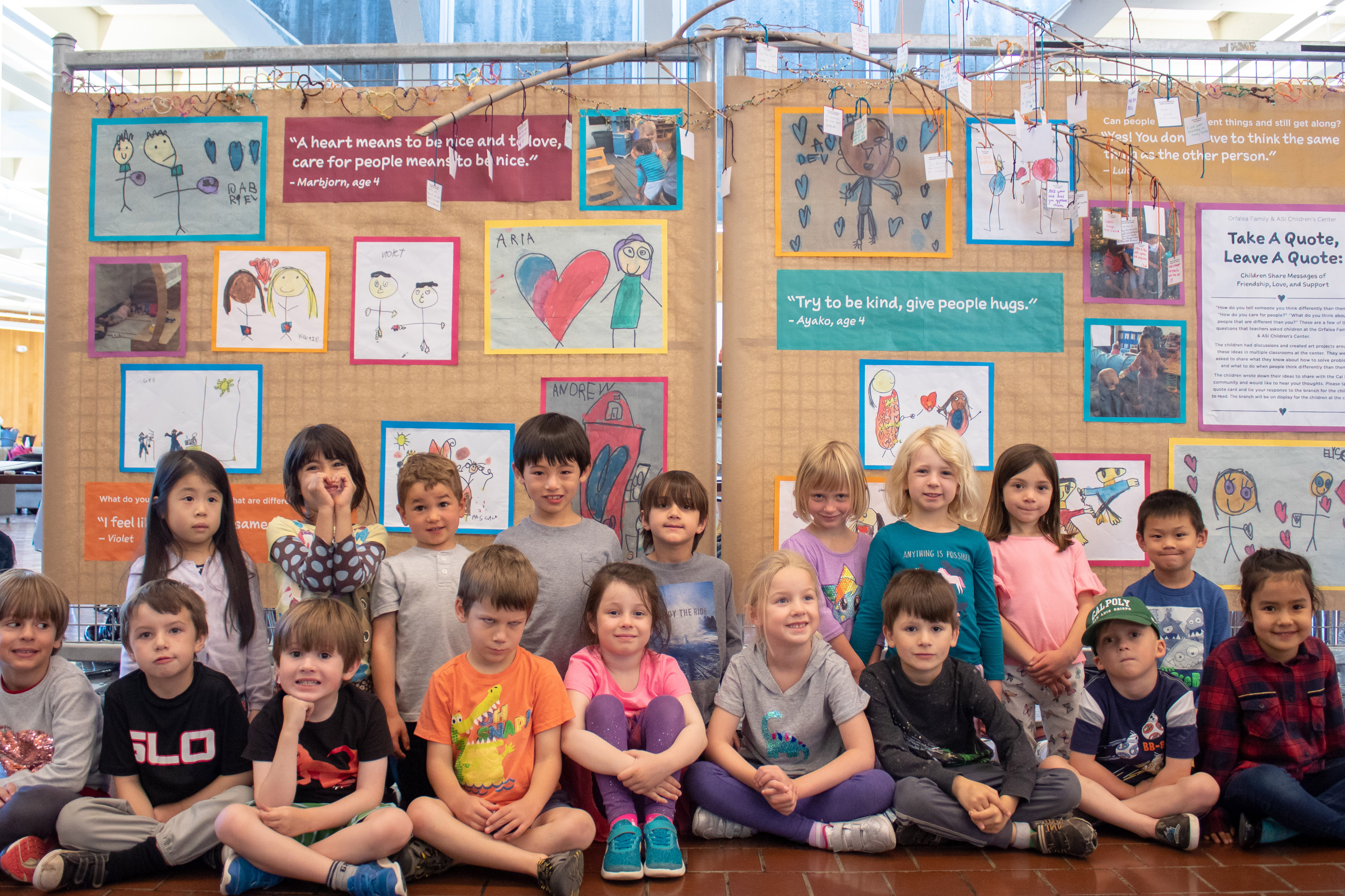 A group of children sit smiling in front of their display featuring art they drew in the University Union