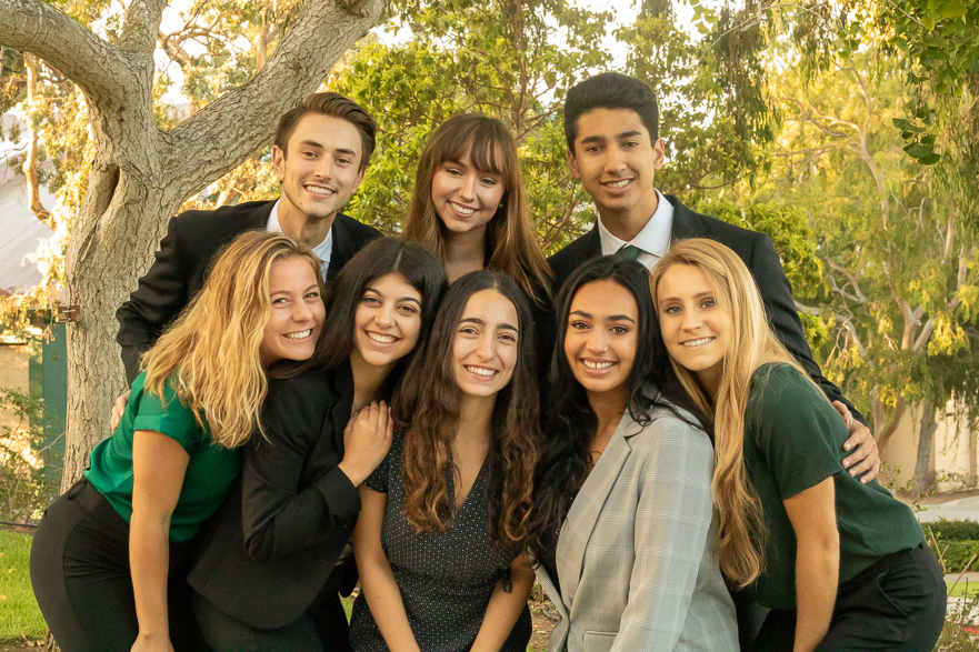 Eight students on the ASI Executive Cabinet smile while standing in a group in front of trees