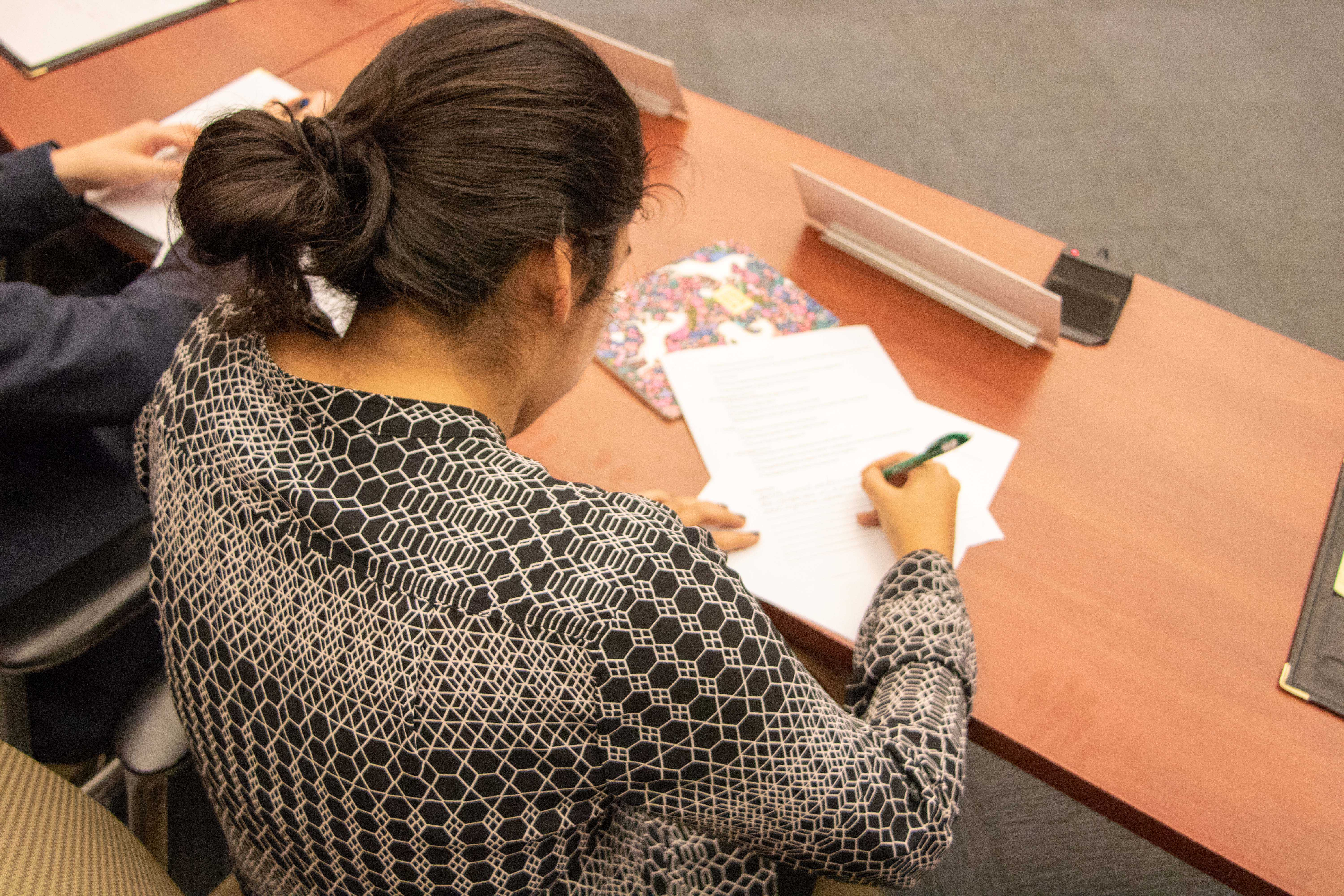 A student sits at a desk and fills out a form