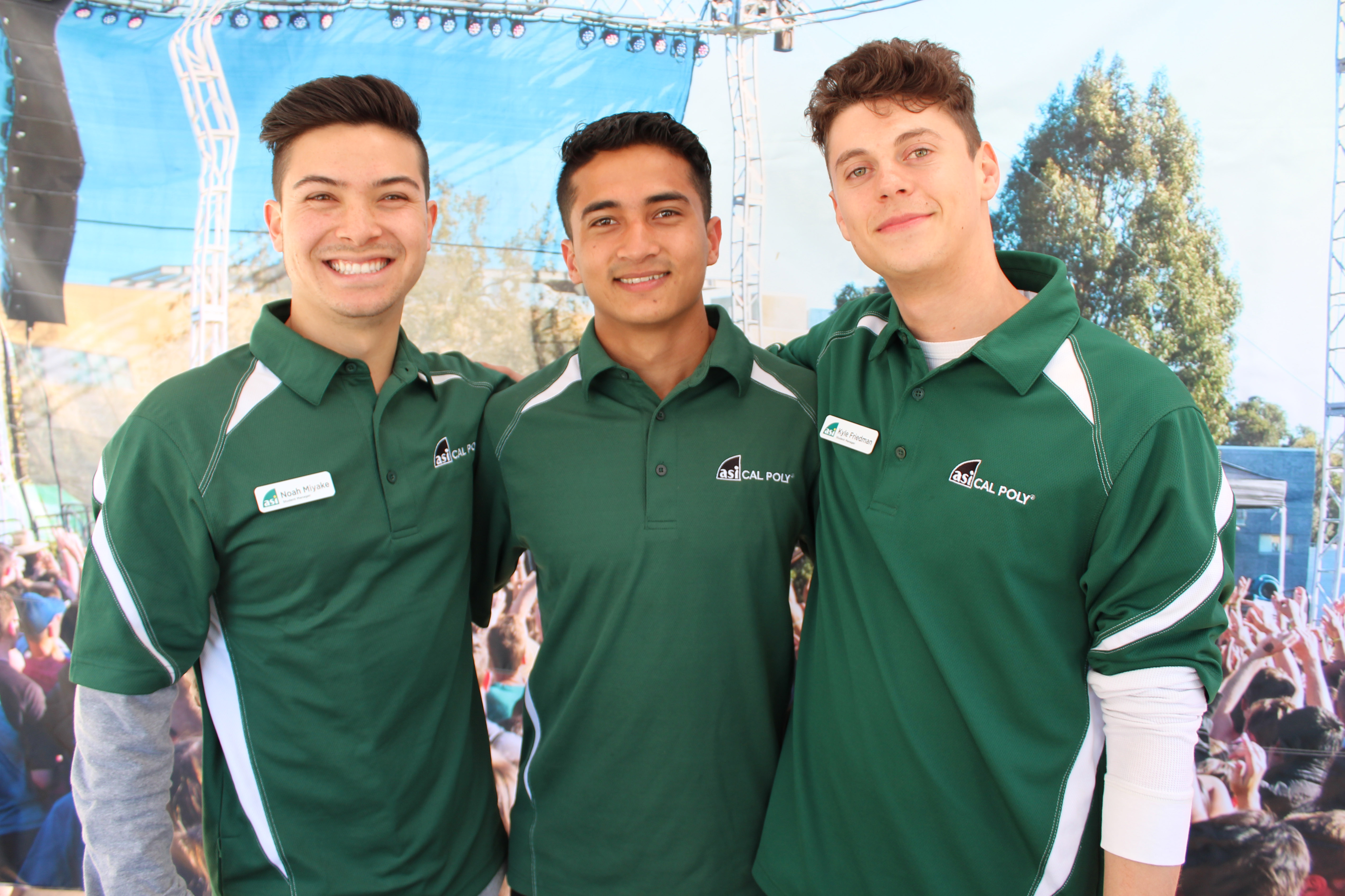 Three male students wearing green ASI polo shirts smile
