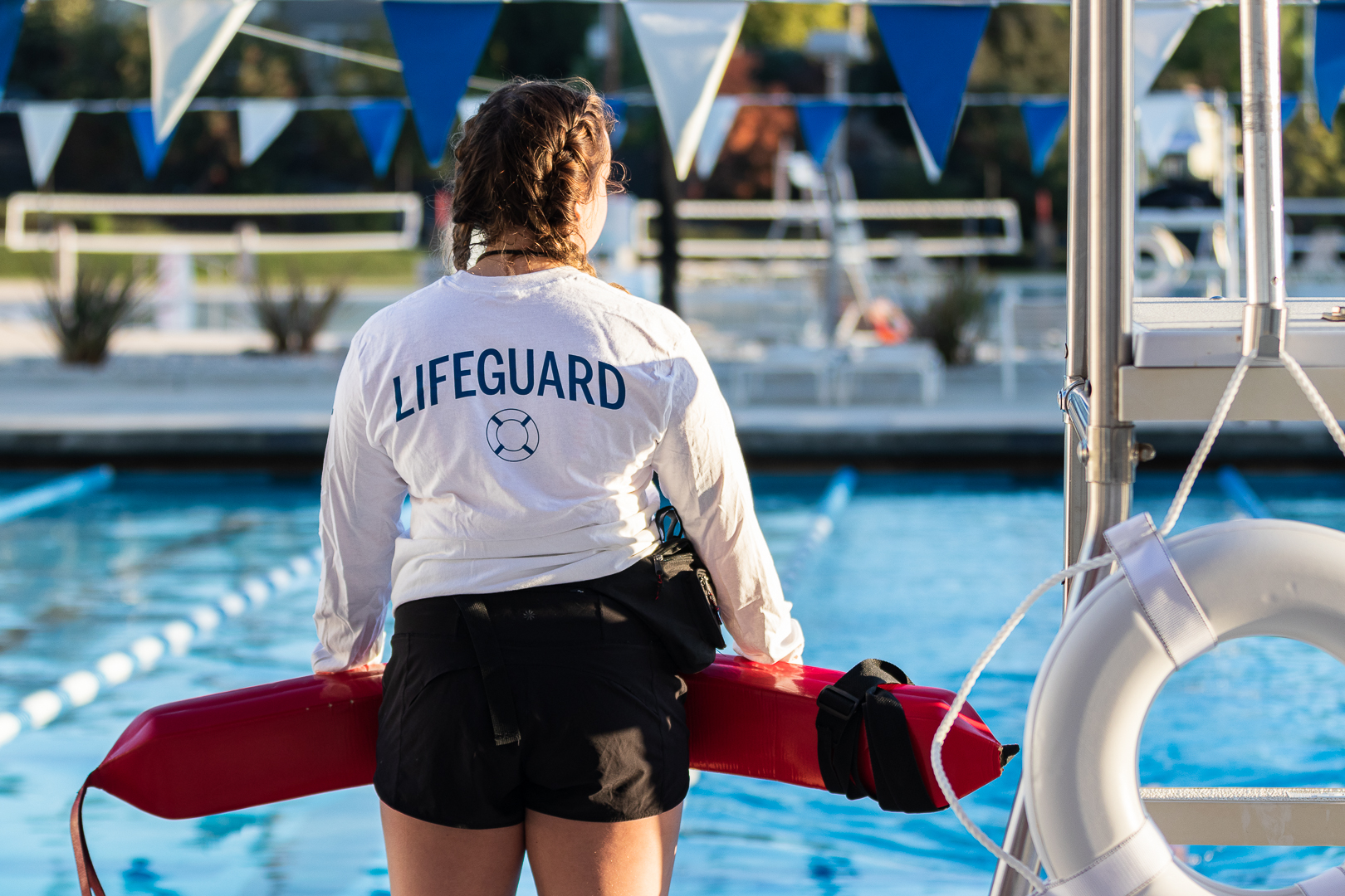 An ASI lifeguard stands looking over the pool with a flotation device