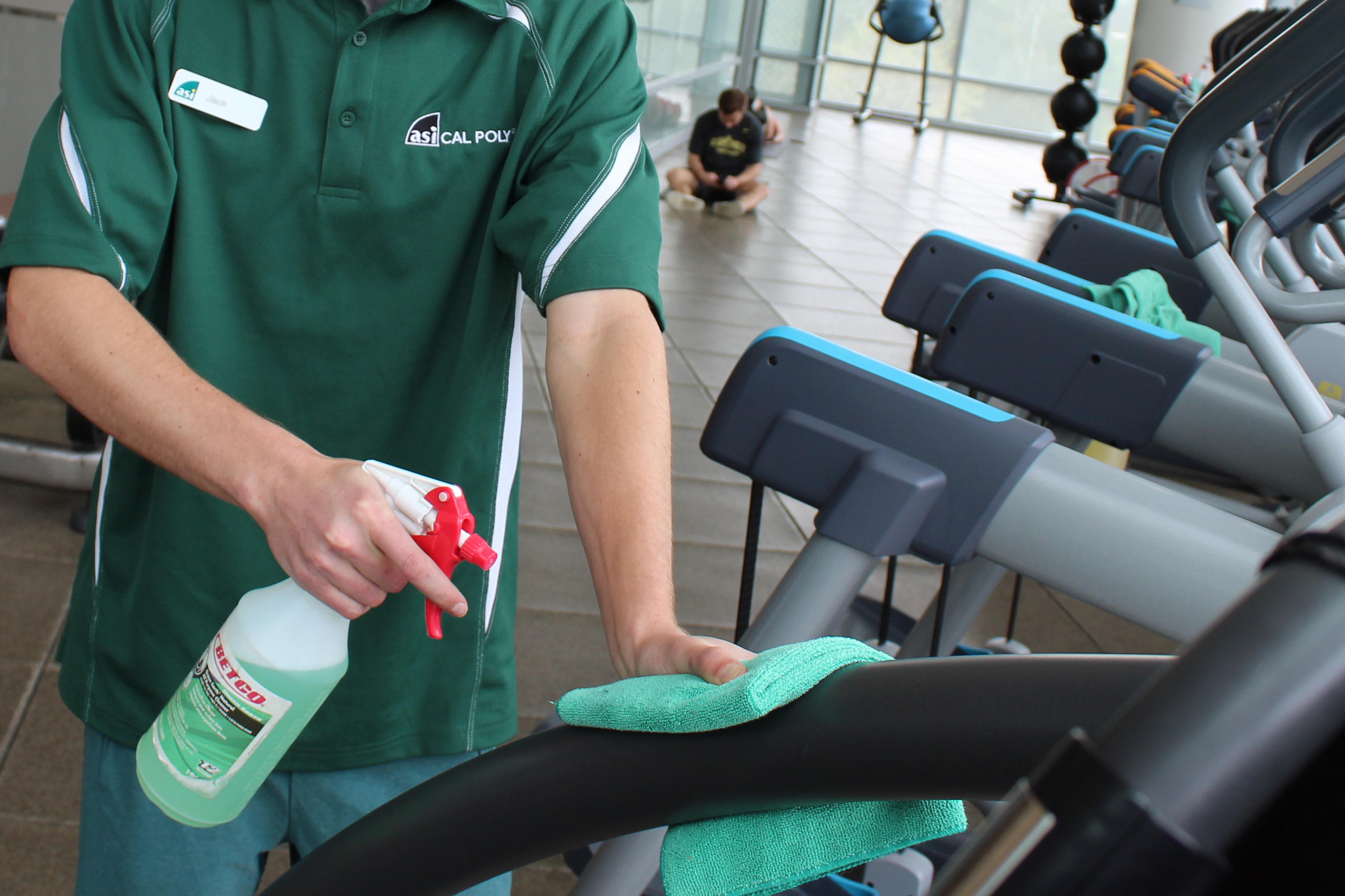 A staff member cleans a machine at the Recreation Center.