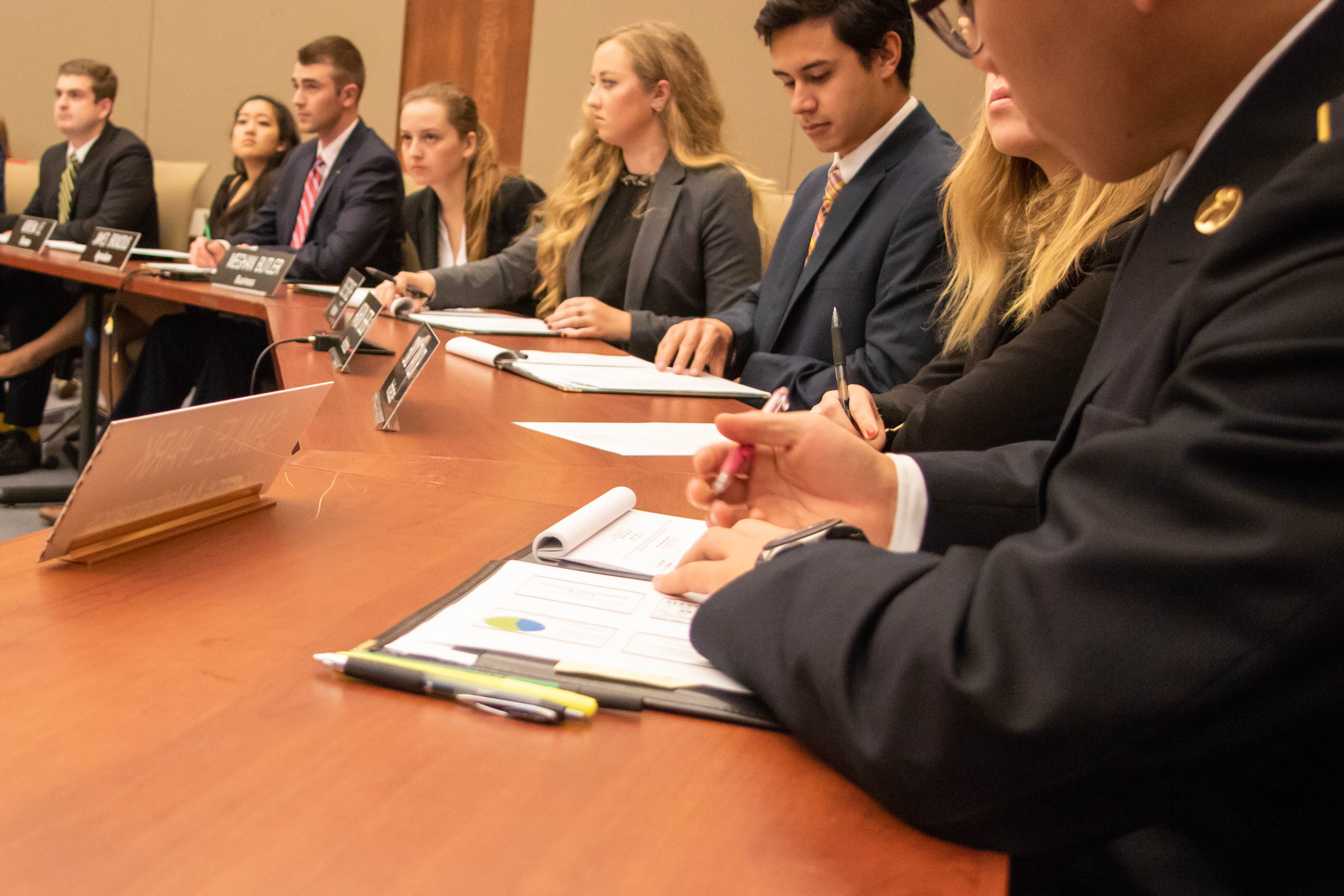 Students sit at a table and take notes at a board meeting