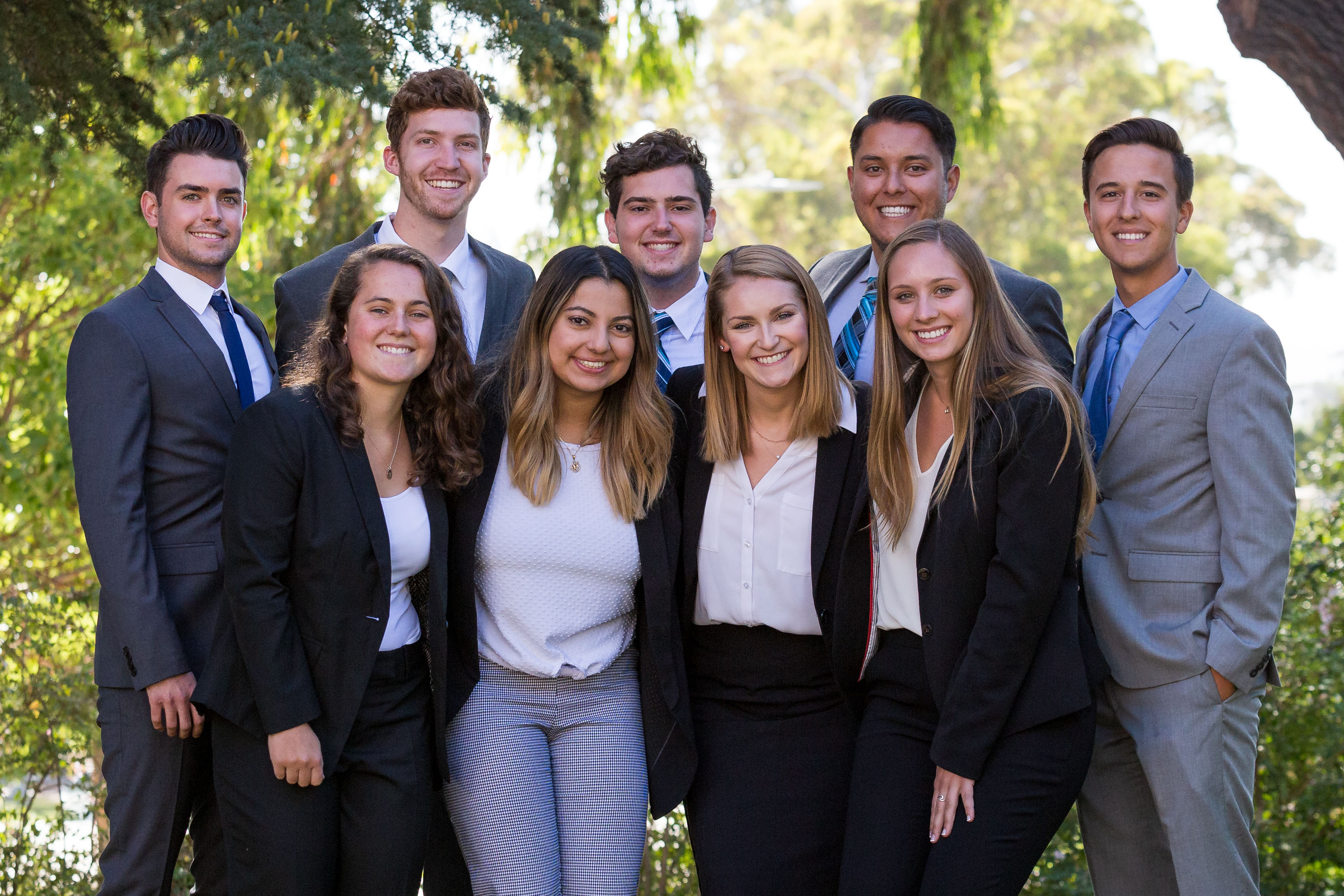 The 9 members of the 2019–20 UUAB stand smiling in a group in business attire